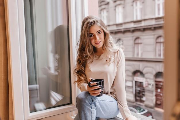 Застенчивая женщина в джинсах сидит на подоконнике и с интересом позирует Бесплатные Фотографии