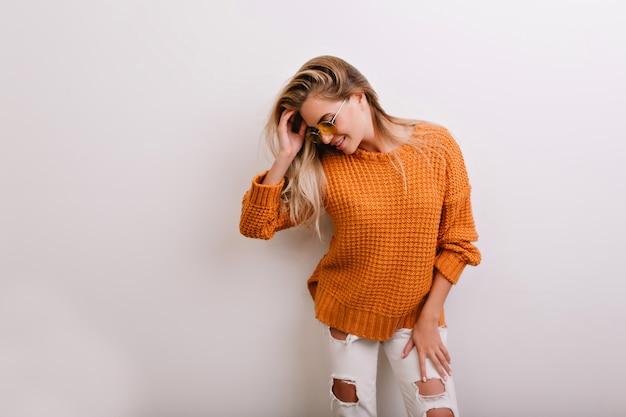 Застенчивая женщина в рваных джинсах смотрит вниз с нежной улыбкой на белом фоне Бесплатные Фотографии