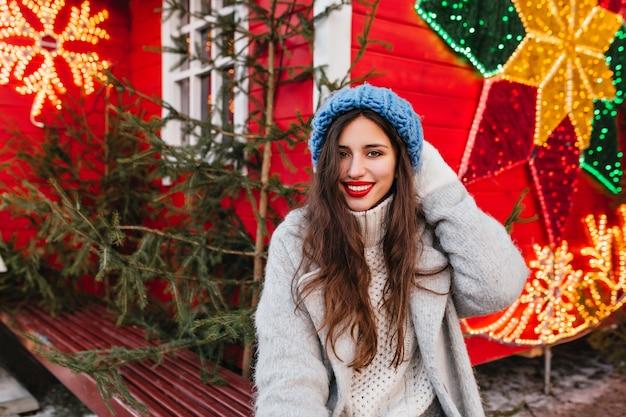 新年のフェアに時間を費やし、緑の木々に近いポーズをとって長い茶色の髪を持つ恥ずかしがり屋の女性。赤いクリスマスの装飾に灰色のコートに立っての壮大な白人女性の屋外写真。 無料写真