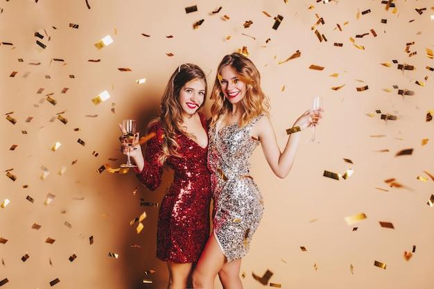 친구와 샴페인 잔을 올리는 빨간 드레스에 수줍은 젊은 여자 무료 사진