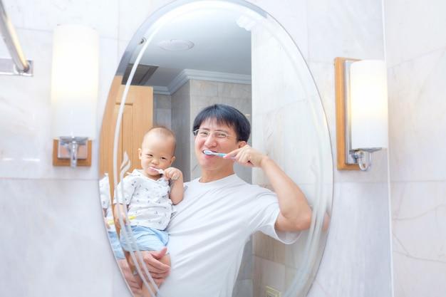 Sian father teaching kid teeth brushing, cute little asian 18 months / 1 year old baby boy child brushing teeth Premium Photo