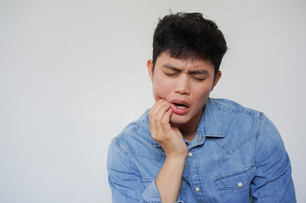 Sian man using hand to massage cheek cause from toothache (wisdom tooth) at clinic Premium Photo