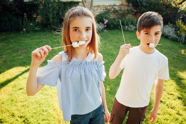 Sibling eating marshmallow and looking at camera Free Photo
