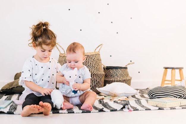 Sibling playing with toys on striped rag Free Photo
