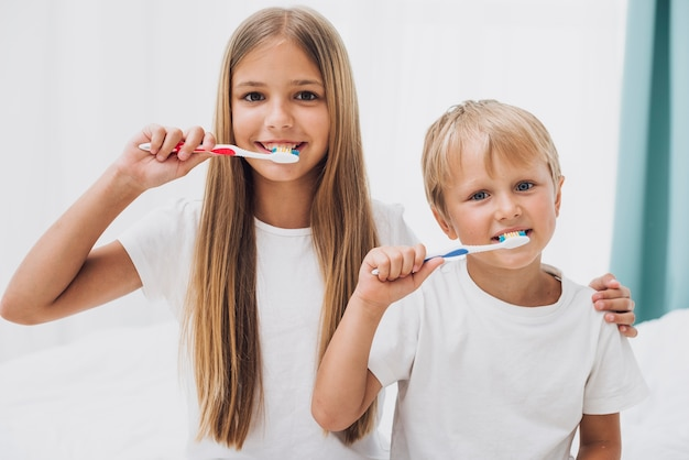 Siblings brushing their teeth together Free Photo