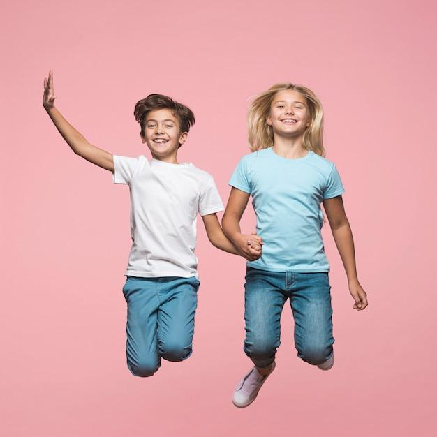 Братья и сестры, взявшись за руки и прыжки Бесплатные Фотографии