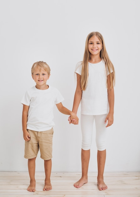 Siblings holding hands while looking at the camera Free Photo