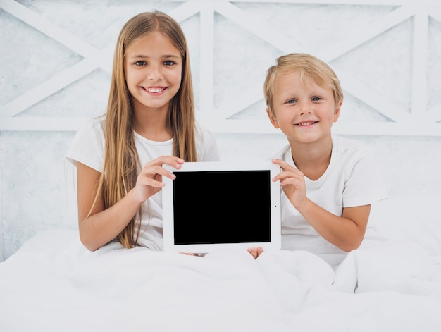 Siblings holding a tablet mock-up Free Photo