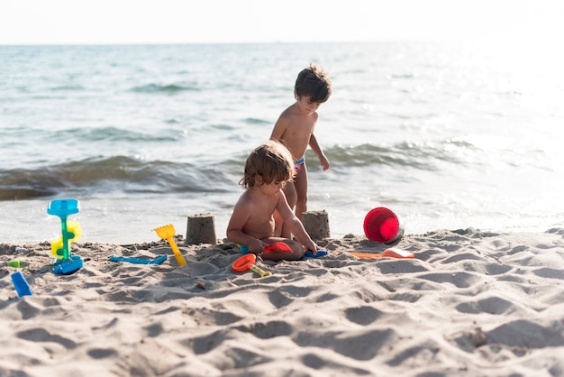 Siblings making sandcastles by the seaside Free Photo