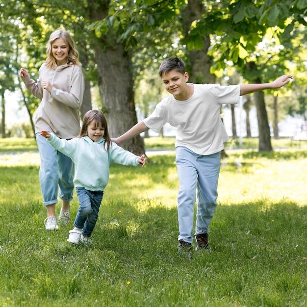 Fratelli e mamma che corrono insieme Foto Gratuite