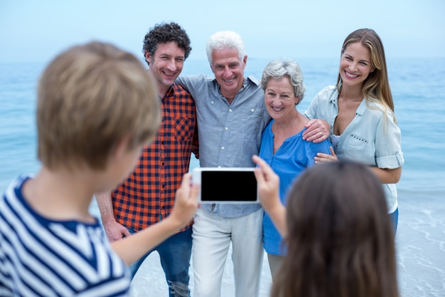 Siblings photographing family with mobile phone Premium Photo
