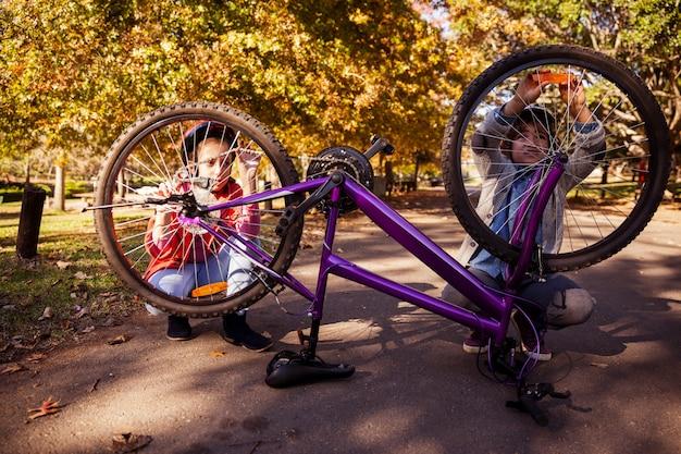 Братья и сестры ремонтируют велосипед Premium Фотографии