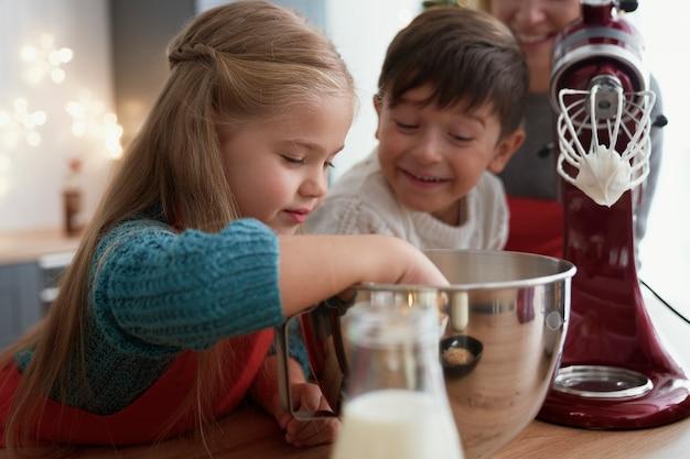 Fratelli germani degustazione pasta di zucchero durante la cottura con la famiglia Foto Gratuite