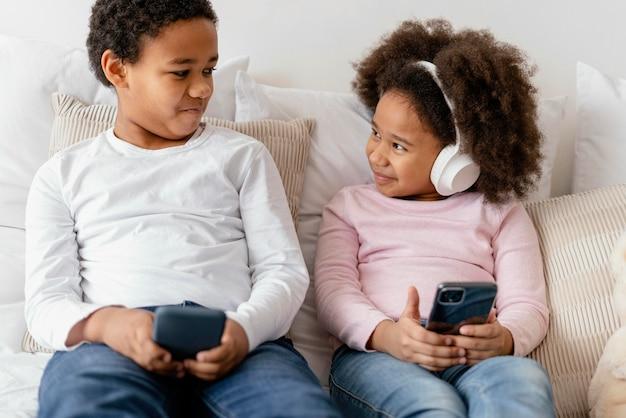 휴대폰을 사용하는 형제 자매 무료 사진