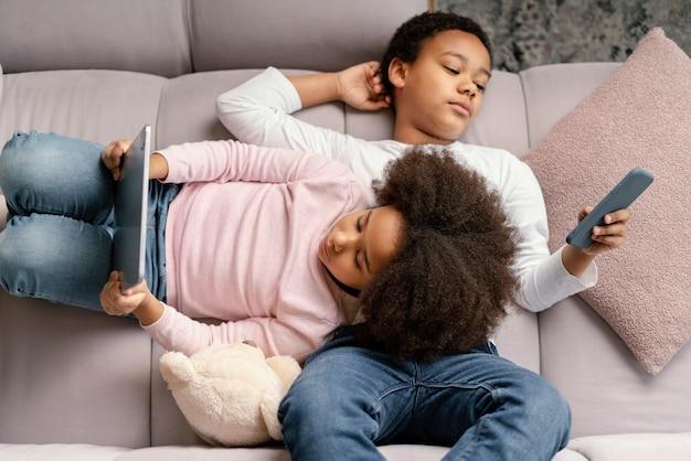 自宅でタブレットとモバイルを使用している兄弟 無料写真
