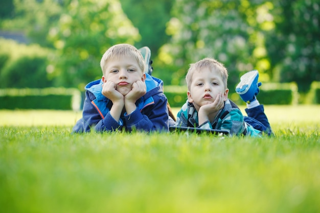 Siblings using a tablet, yingon grass in the park in suny day Premium Photo