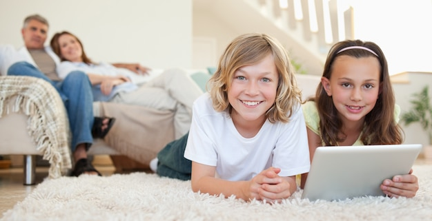 Siblings with tablet on the carpet Premium Photo