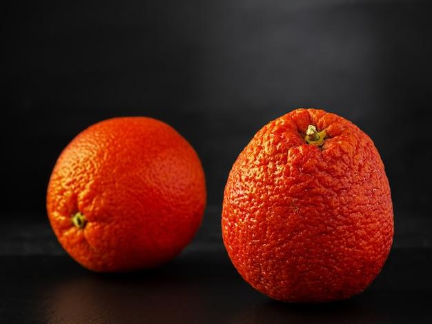 Arancia rossa siciliana situata su una superficie di pietra nera Foto Gratuite