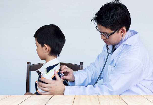 Sick asian boy being examined by male doctor over white background Free Photo