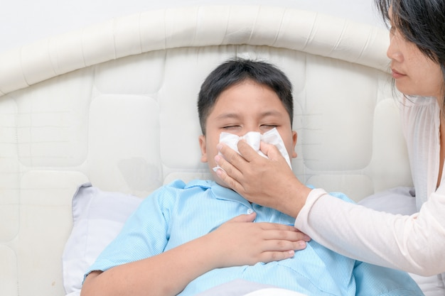 Sick asian child wiping or cleaning nose with tissue Premium Photo