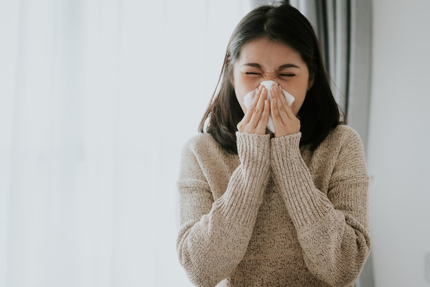 ティッシュを使用して自宅でくしゃみをする病気のアジアの女性 Premium写真
