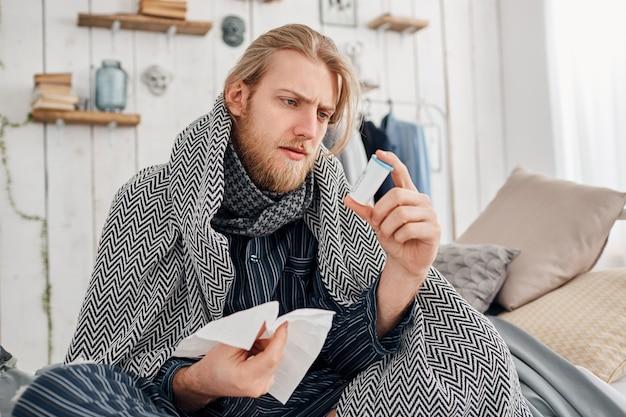 Больной бородатый светловолосый мужчина в пижаме сидит на кровати, окруженной одеялом и подушками, хмурится, читая рецепт на таблетках, держит в руке носовой платок. проблемы со здоровьем, простуда и грипп. Бесплатные Фотографии