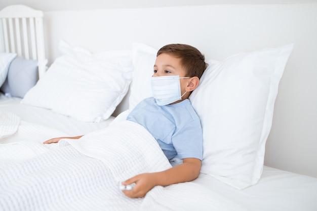 Больной мальчик лежит в постели с медицинской маской Premium Фотографии