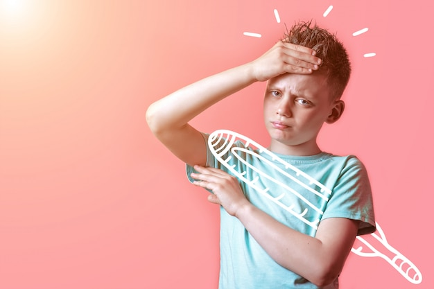Sick boy in light t-shirt measures the temperature of a thermometer on a colored Premium Photo