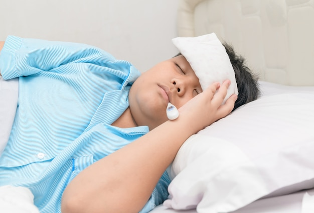 Sick boy with thermometer in mouth and compress on forehead. Premium Photo
