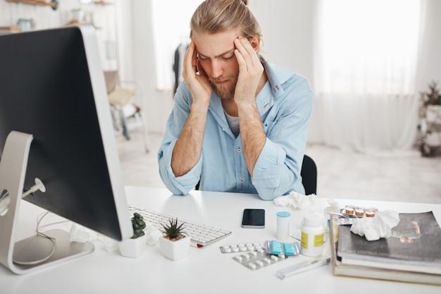 Uomo caucasico malato seduto in ufficio, stringendo le tempie a causa del mal di testa, lavorando sul computer, guardando lo schermo con un'espressione dolorosa sul viso, cercando di concentrarsi, circondato dalla medicina Foto Gratuite