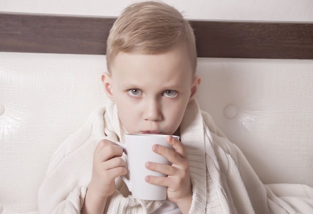 The sick child sitting in a bed and holds a cup of tea. medicine concept. Premium Photo