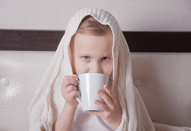 The sick child sitting in a bed and holds a cup of tea Premium Photo