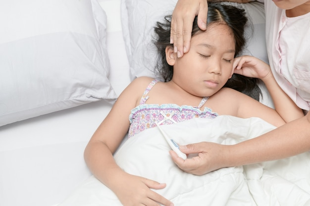 Sick child with high fever laying in bed Premium Photo