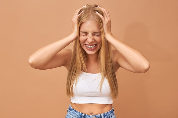 Sick frustrated teenage girl closing her eyes, squeezing head Free Photo