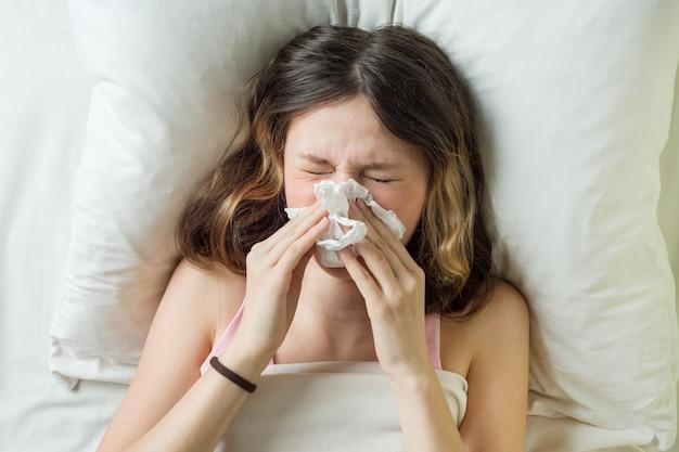 Sick girl on bed sneezing in handkerchief in bedroom Premium Photo