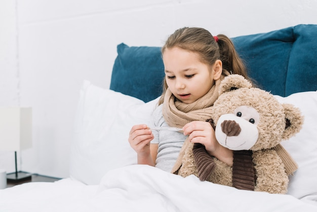 Sick girl sitting on bed with teddy bear looking at thermometer Free Photo