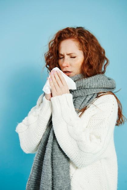 Ragazza malata che starnutisce e si pulisce il naso Foto Gratuite