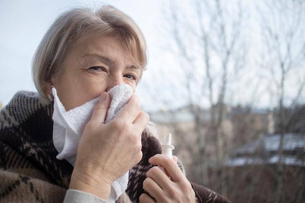 病気の病気の年配の成熟した女性が滴り、鼻を詰まらせるために点鼻薬を注射します。鼻水で引退した女性は、ハンカチで鼻をかむ、薬のスプレー、丸薬を手に持っています。副鼻腔炎の治療 Premium写真