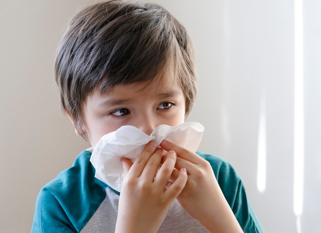 Sick kid blowing nose into tissue Premium Photo