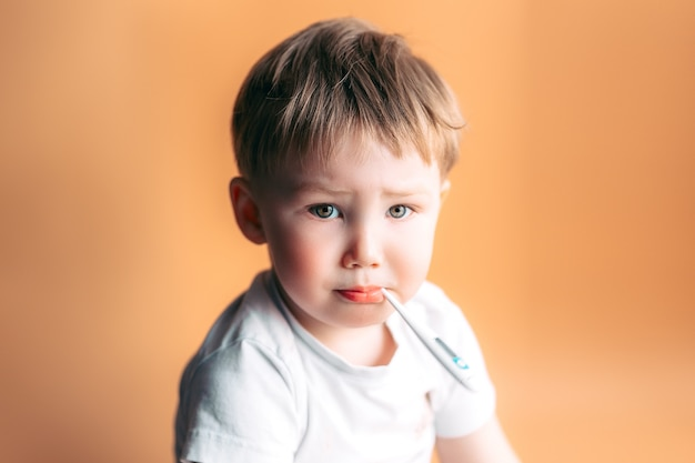 Sick kid with a thermometer in his mouth with sad face on orange background Premium Photo