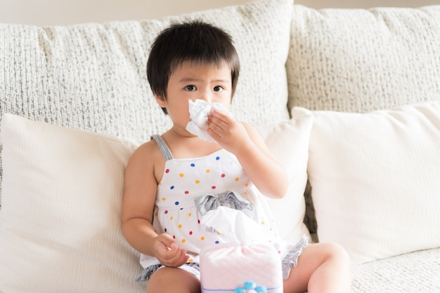 Sick little asian girl wiping or cleaning nose with tissue sitting on sofa at home Premium Photo
