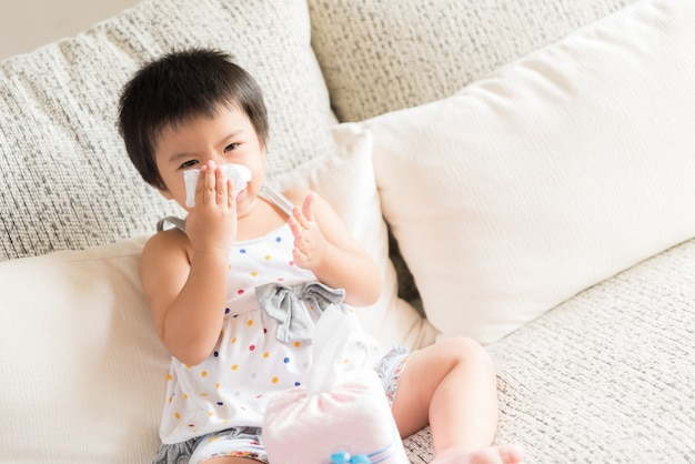 Sick little asian girl wiping or cleaning nose with tissue Premium Photo