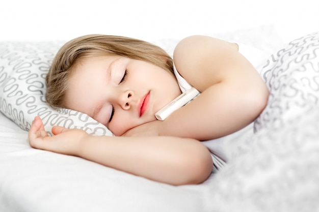 Sick little child girl lying in bed with thermometer Premium Photo