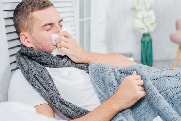 Sick man blowing his nose with white tissue paper lying on bed Free Photo