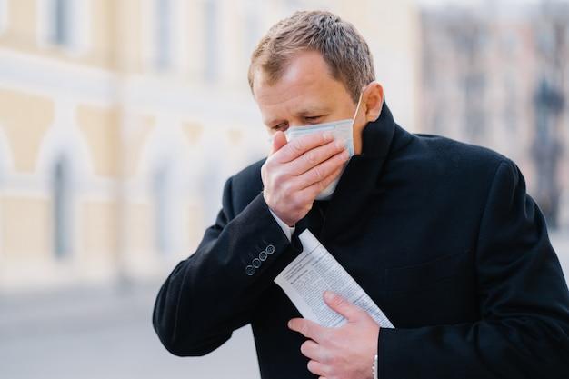 病人は咳をし、手のひらで口を覆い、医療用マスクを着用し、アレルギー、インフルエンザ、インフルエンザ、またはコロナウイルスの症状があり、屋外を散歩し、新聞を持って、気分が悪くなります。 covid-19、隔離コンセプト Premium写真