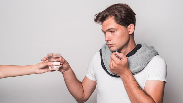 Sick man holding capsule taking glass of water from person's hand Free Photo