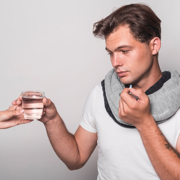 Sick man holding glass of water from person's hand taking capsule Free Photo