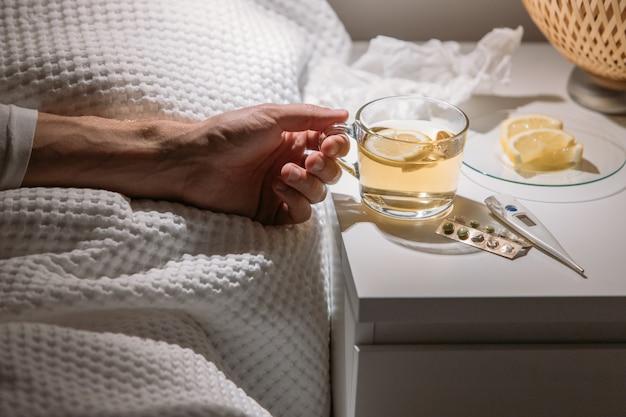 Больной человек в постели держит чашку горячего чая с лимоном, пьет горячий напиток, чтобы выздороветь от гриппа, лихорадки и вирусов. Premium Фотографии