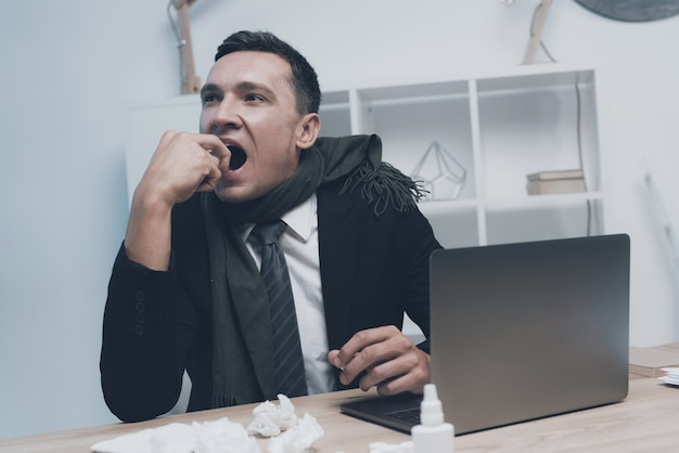 A sick man is sitting at his workplace in the office Premium Photo