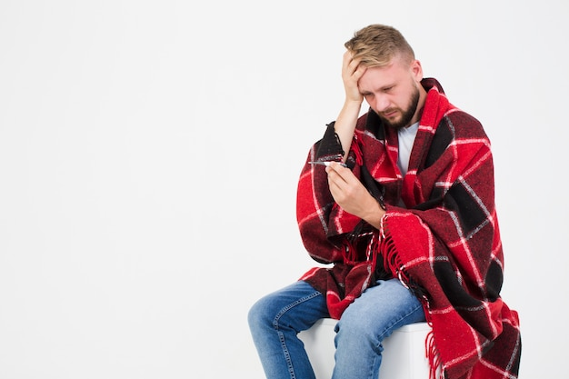 Sick man looking at thermometer Free Photo